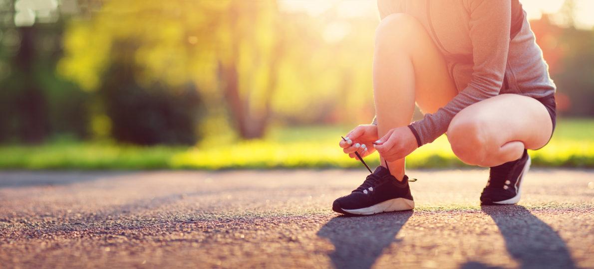 Femme en train de lacer ces baskets pour partir faire un jogging
