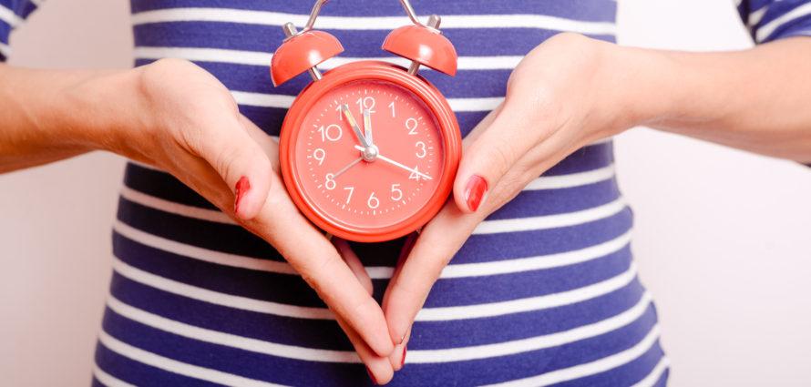 Femme en train de tenir une horloge dans ses mains