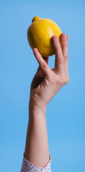 Main de femme portant un citron