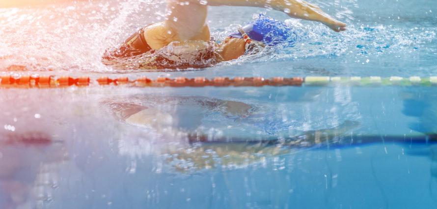 Femme en train de nager dans une piscine