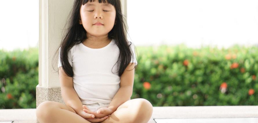 Petite fille assise en tailleur avec les yeux fermés