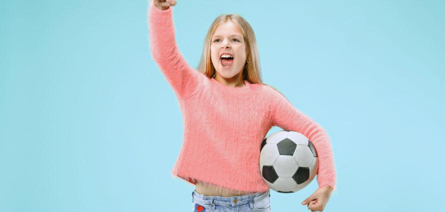 Jeune fille avec le point levé et un ballon de foot sous le bras
