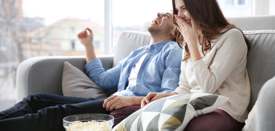 Young,Couple,Watching,Tv,On,A,Sofa,At,Home
